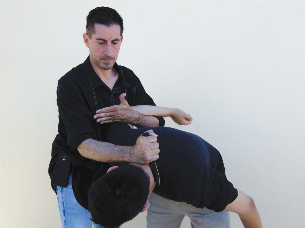 2 men using defense moves with knife