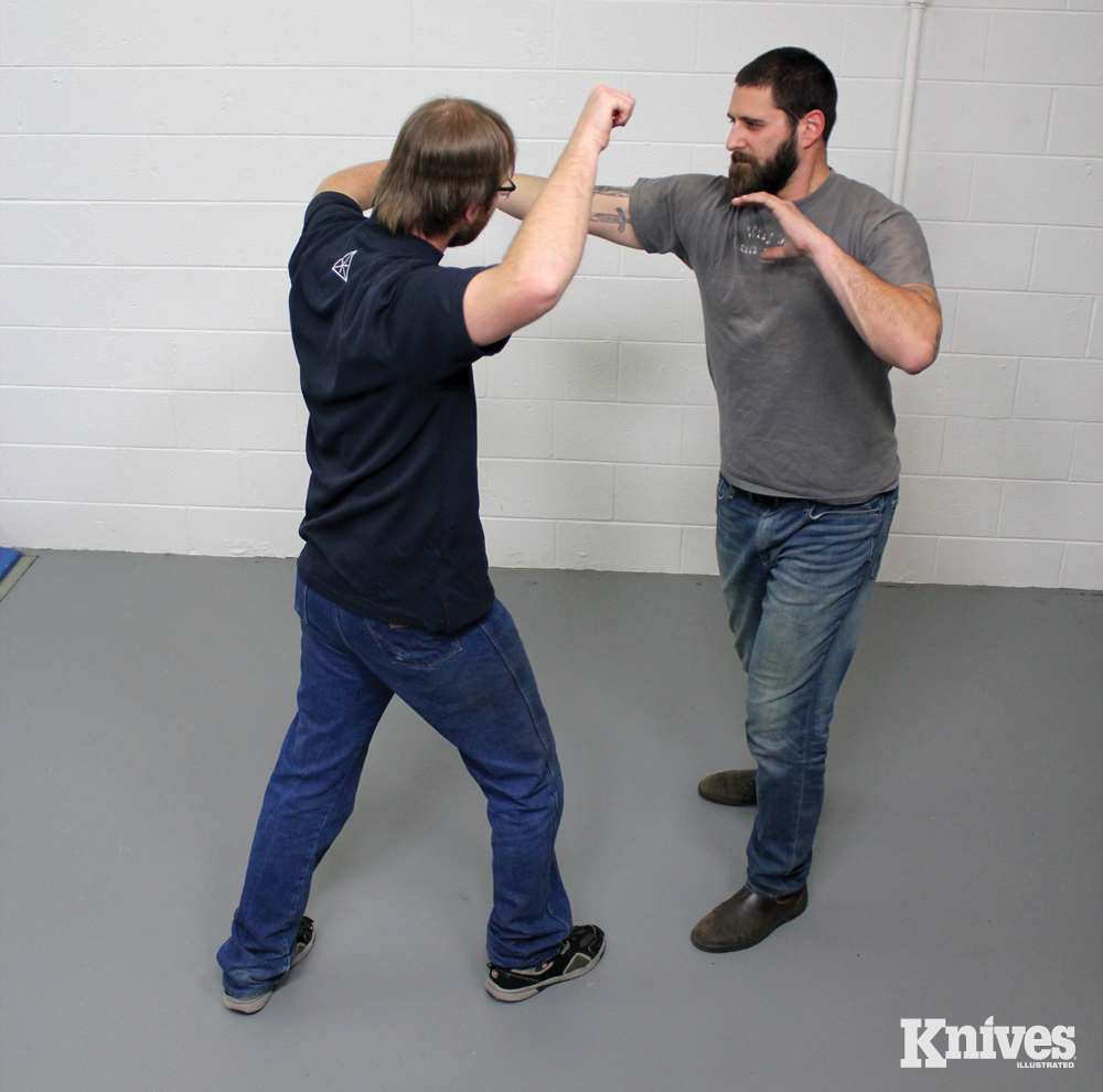 He follows by grabbing the attacker's wrist and prepares for his next cut.